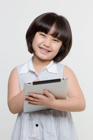 Little asian girl smiling and holding tablet computer on isolated background 免版税图像