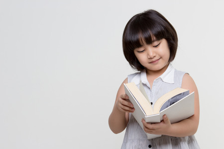 Portrait of little lovely Asian child reading a book Stock Photo - 39229929