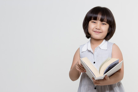 Portrait of little lovely Asian child reading a book