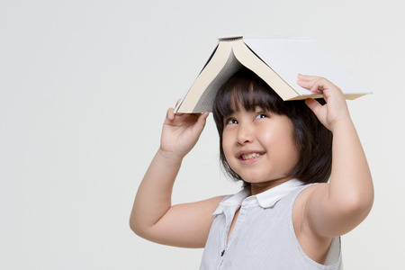 Portrait of little Asian child thinking and put a book on top with copy space Stock Photo