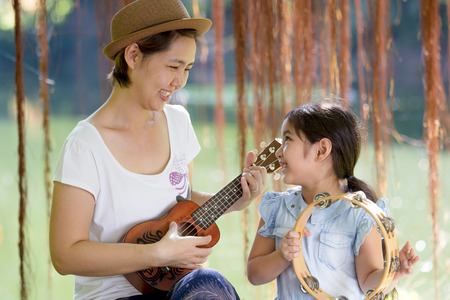 acoustic ukulele: Asian mother playing ukulele with herdaughter in park