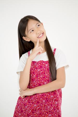 Portrait of happy little Asian child thinking on isolated background Stock Photo