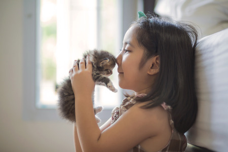 Adorable little asian girl holding her kitten