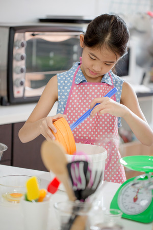 ethnic mix: Little Asian cute chef cooking a bakery in kitchen Stock Photo