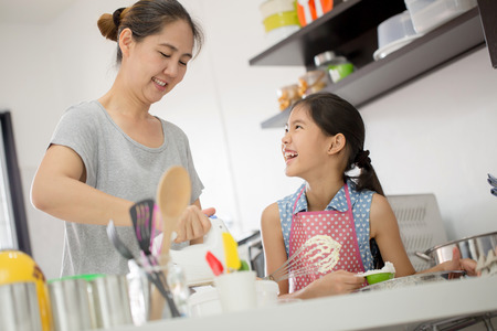 Little Asian cute chef cooking a bakery in kitchen with mother Stock Photo - 52706199