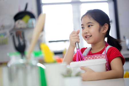 asian bowl: Little Asian cute chef cooking a bakery in kitchen Stock Photo