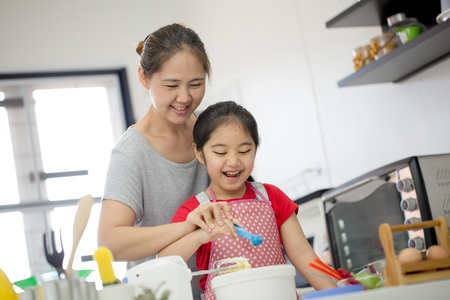 kid's day: Little Asian cute chef cooking a bakery in kitchen with mother
