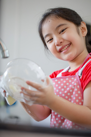 household tasks: Close up of little Asian girl washing dishes in the kitchen