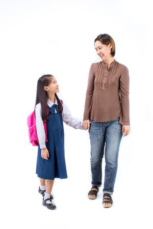 Portrait of asian child in school uniform holding hand with mother on white background isolated Stock Photo