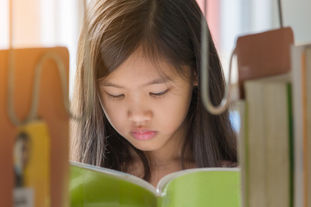 Little Asian girl reading a book in library at school Stock Photo