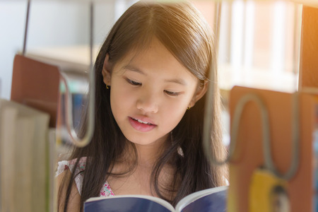 thai ethnicity: Little Asian girl reading a book in library at school Stock Photo