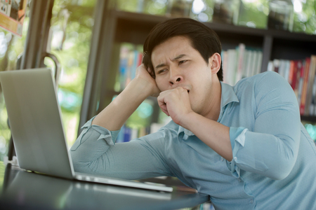 Sleepy young Asian worker with laptop computer, Hard work Banque d'images