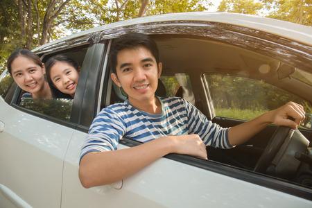 ミニバンに幸せなアジア家族が笑顔やバカンス旅行の運転 写真素材