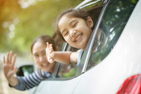Happy Asian little girl playing on window car with mother, Family traveling on countryside