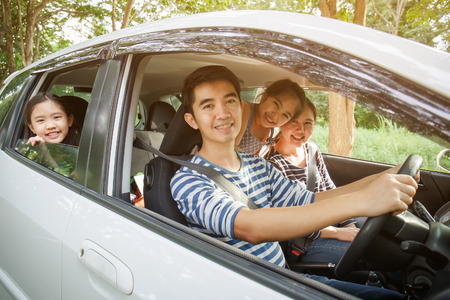 Happy Asian family on mini van are smiling and driving for travel on vacation 免版税图像
