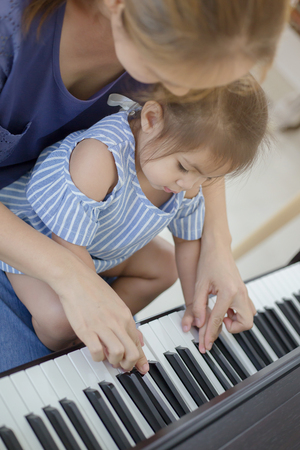 Happy little Asian girl playing piano with mother at home