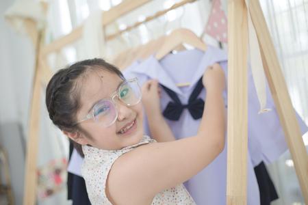 Little Asian student choosing and dressing school uniform prepare to go school, Back to school