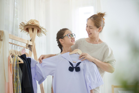 Happy Asian mother helping daughter dressing her's uniform prepare to school, Back to school 版權商用圖片 - 82966442
