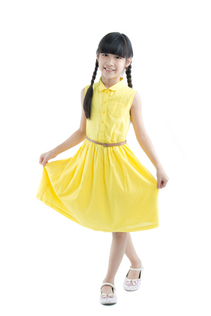 Happy long hair little Asian child smiling and dancing isolated on white