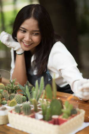 Portrait young Asian girl planting little cactus in a pot for her hobby