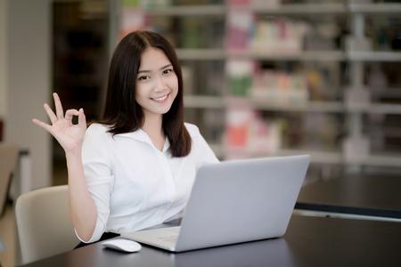 Retrato de una bella mujer asiática feliz usando laptop en la oficina