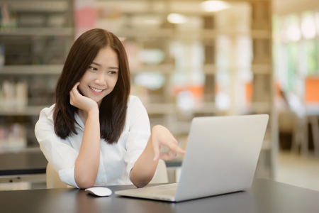 Portrait of a happy beautiful Asian young woman using laptop in office
