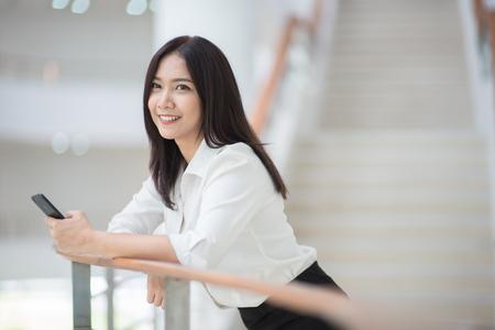 事務所ビルにおける携帯電話の若いアジア女性管理職 写真素材