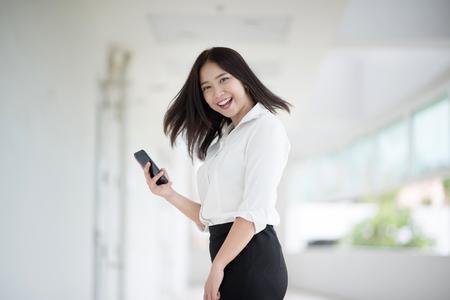 Jonge Aziatische vrouw stafmedewerker die met een mobiele telefoon in de bureaubouw werkt