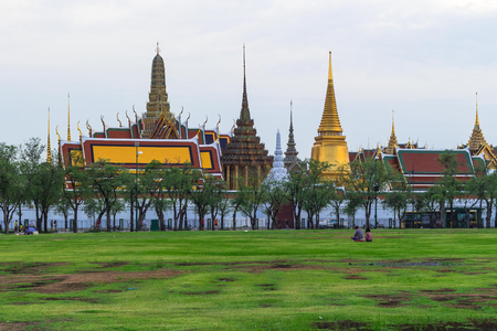 View of The Grand Palace and The Emerald Buddha temple from Sanam Luang park in the afternoon where people relaxing and strolling around Editorial