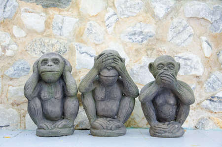 Three wise monkeys with stone background Stock Photo