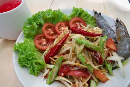 papaya and shrimp salad on white plate