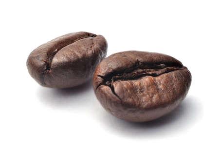 frijoles: Cerca de dos oscuros granos tostados de caf� de comercio justo en un fondo blanco