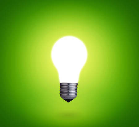 idea concept whit one glowing light bulb on green background  Banco de Imagens
