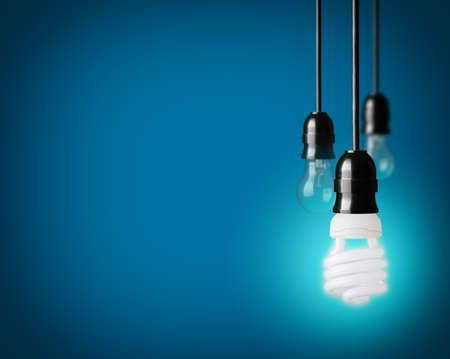 enchufe de luz: Bombillas y bombilla de ahorro de energ�a en el fondo azul