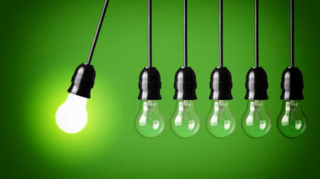 Idea concept on green background  Perpetual motion with light bulbs Stockfoto