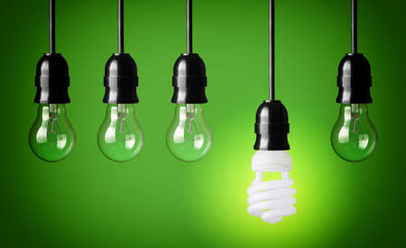 energy conservation: Idea concept with light bulbs and energy save bulb  Green background