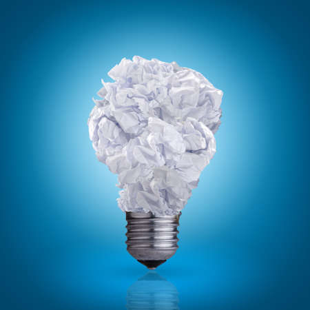 old desk: light bulb made of crumpled paper on blue background