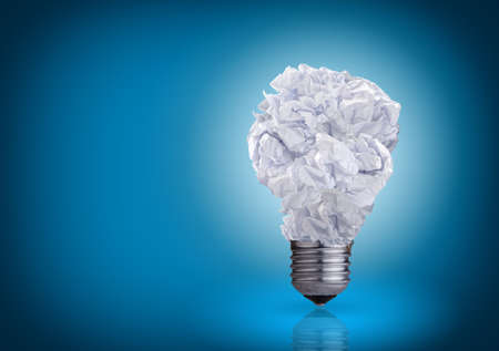power failure: light bulb made of crumpled paper on blue background