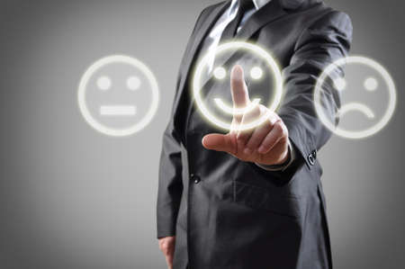 appraise: Businessman hand choosing smile on touch screen Stock Photo