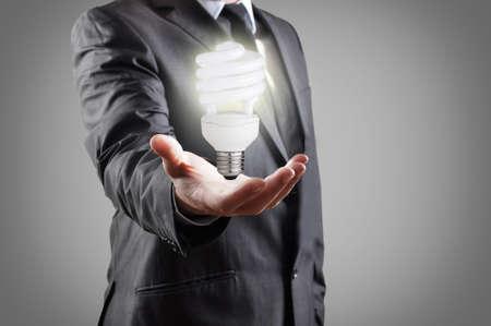 ahorro energia: Bombilla de ahorro de energía en la mano del hombre de negocios