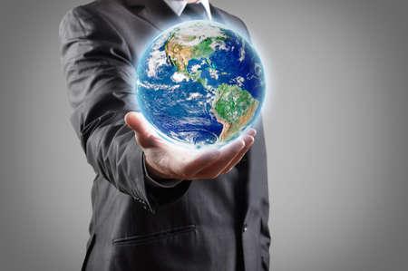 mundo manos: Hombre de negocios tiene tierra en una mano Foto de archivo
