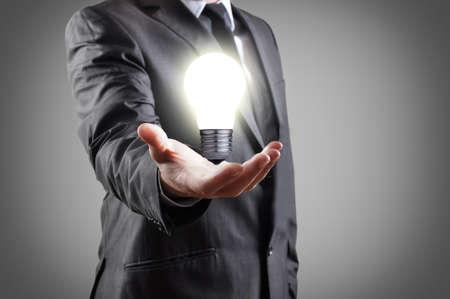 enchufe de luz: Bombilla en la mano del hombre de negocios
