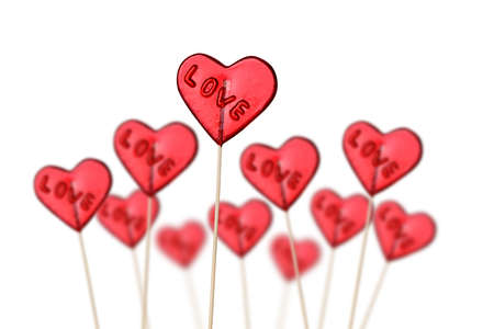 Red heart shaped lollipops on white background  photo
