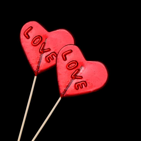 hard candy: Two red heart shaped lollipops on black background