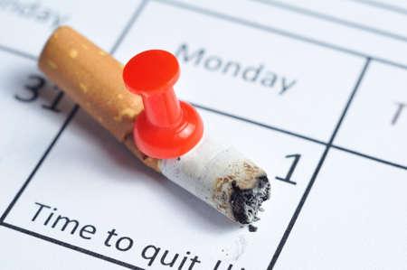 prohibido fumar: Cigarette empalado en el calendario Foto de archivo