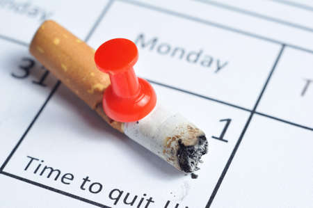no smoking: Cigarette impaled on calendar