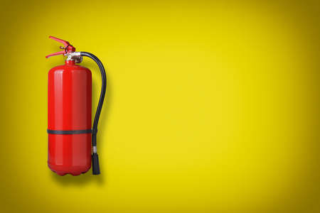 fire extinguisher: Fire extinguisher on the yellow wall