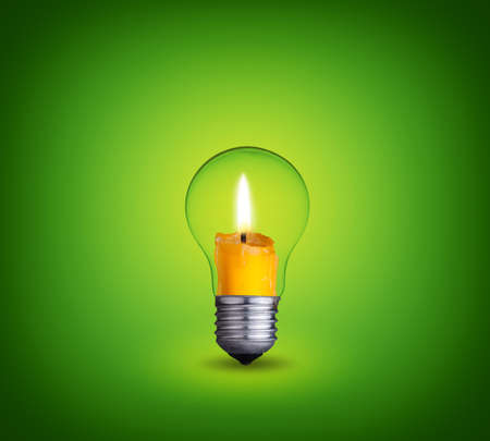 candle into lighting bulb on green background photo