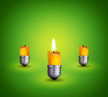 candles into lighting bulbs on green background Idea concept photo