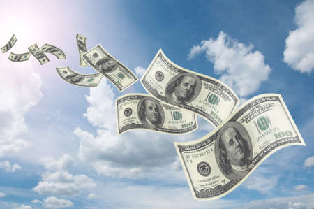 flying dollar bills in flocks in blue sky